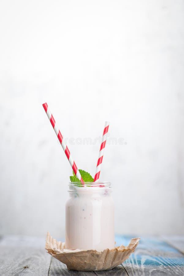 Skorra med att dricka yoghurt, bär och sugrör på trätabellen royaltyfria bilder