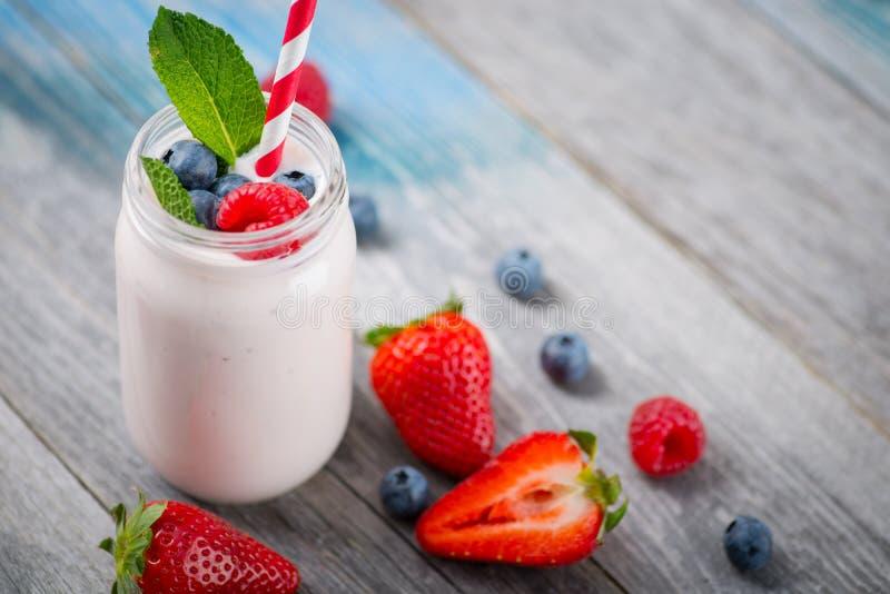 Skorra med att dricka yoghurt, bär och sugrör på trätabellen royaltyfri foto