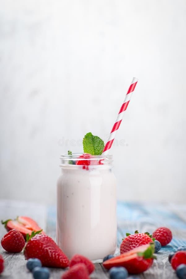Skorra med att dricka yoghurt, bär och sugrör på trätabellen royaltyfri fotografi