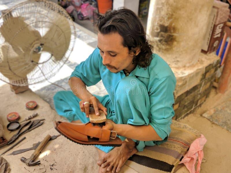Skotillverkare från Pakistan Fattigt arbete som gör hårt arbete royaltyfri bild