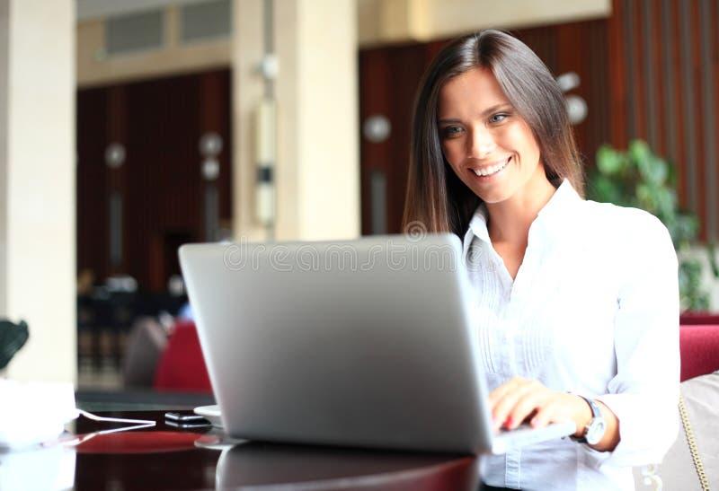 Skott av en attraktiv mogen affärskvinna som arbetar på bärbara datorn i hennes arbetsstation arkivbild