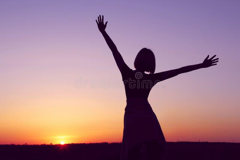 Skott av en bekymmerslös kvinna på stranden mot solnedgången arkivfoto