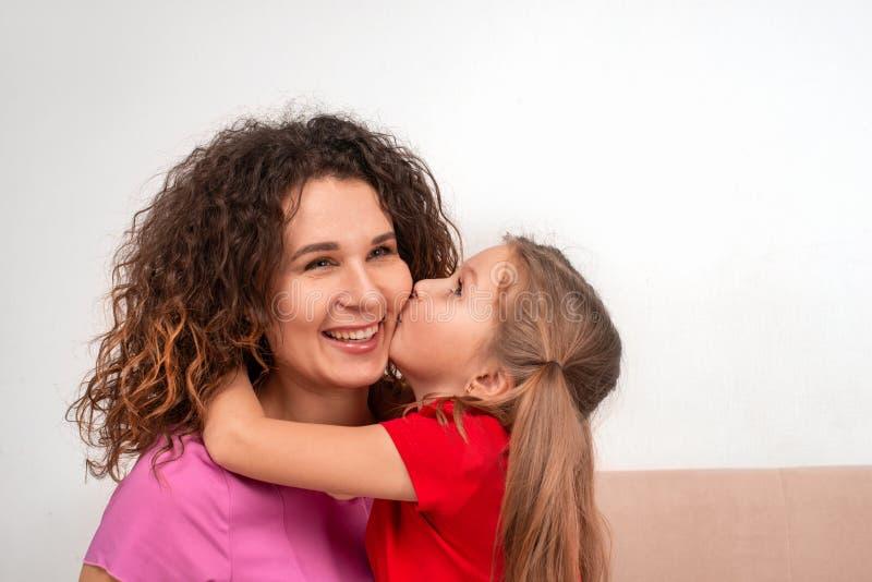 Skott av en cheriful moder och hennes lilla dougter som tillsammans spenderar tid Dotter som kysser mamman på kinden royaltyfri fotografi