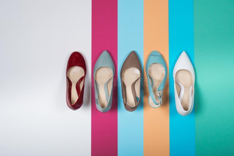 Skott av flera typer av skor på ett färgat papper, flera designer av läderskon Kopiera utrymme för text arkivbild
