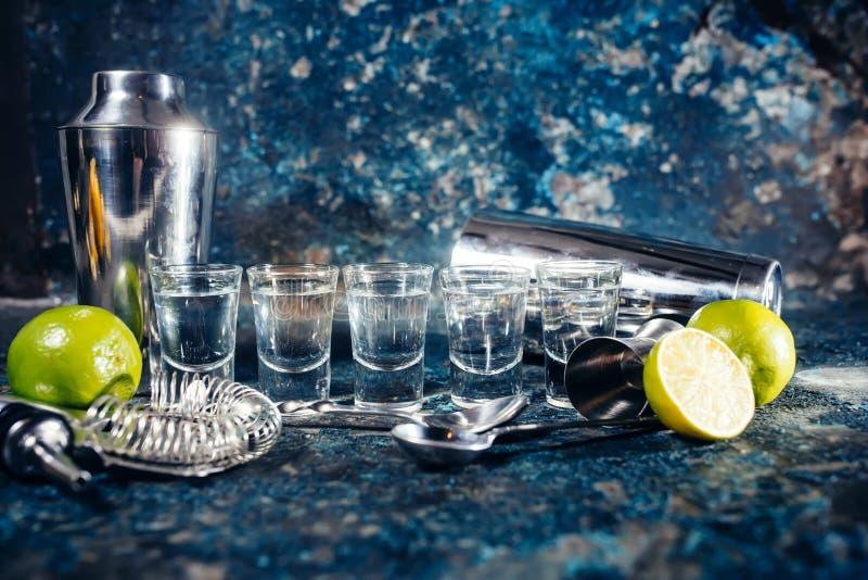 Skott av tequilaen eller den starka drinken i små exponeringsglas, med limefruktgarneringen som är klar att tjänas som royaltyfri fotografi