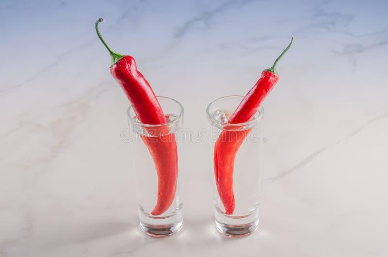 skott av vodka och peppar för röd chili/skott av vodka och peppar för röd chili på en vitmarmorbakgrund Selektivt fokusera fotografering för bildbyråer