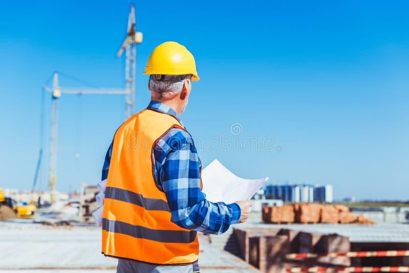 Skott för bakre sikt av byggmästaren i reflekterande väst- och hardhatanseende på konstruktionsplatsen med byggnadsplan arkivbilder