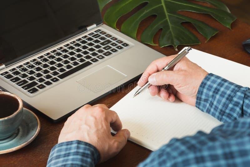 Skott för bakre sikt av för affärsman för händer upptagen handstil vid pennan i anteckningsbok och användabärbar dator på kontors royaltyfri fotografi
