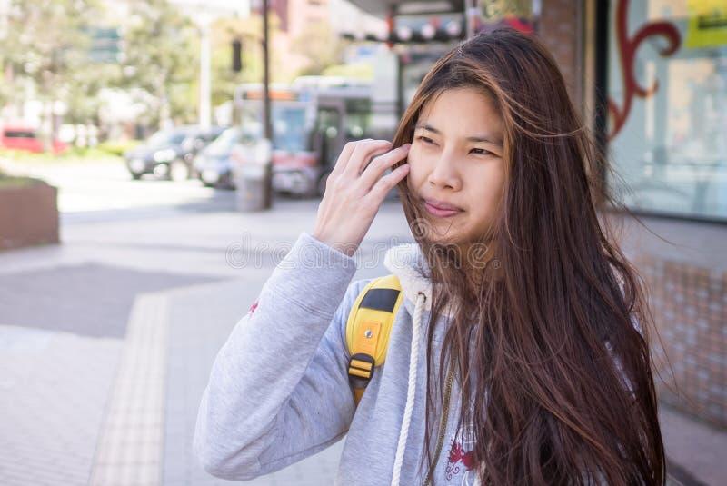 Skott för gata för lång asiatisk handelsresandeflicka för hår utomhus- arkivfoto