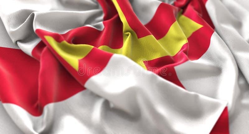 Skott för Guernsey flagga rufsat Beautifully vinkande makronärbild arkivbild