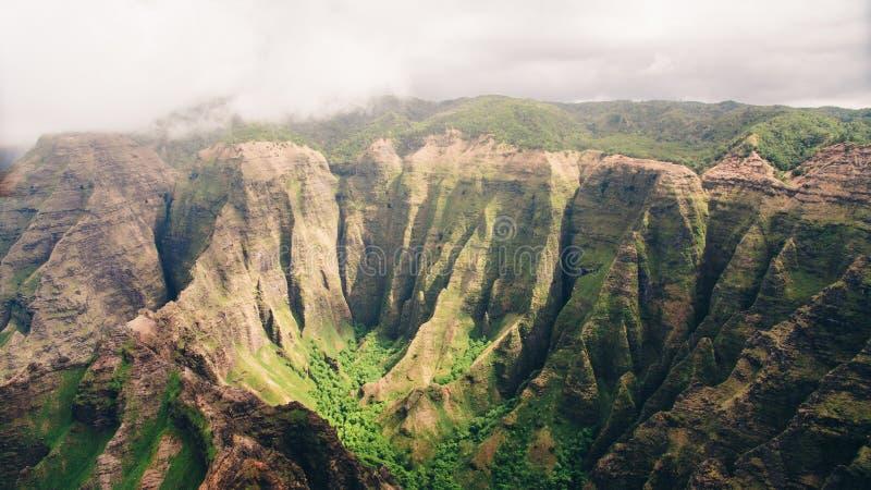 Skott för hög vinkel av ön av Kauai härliga berg i en dimma med grönska royaltyfri fotografi