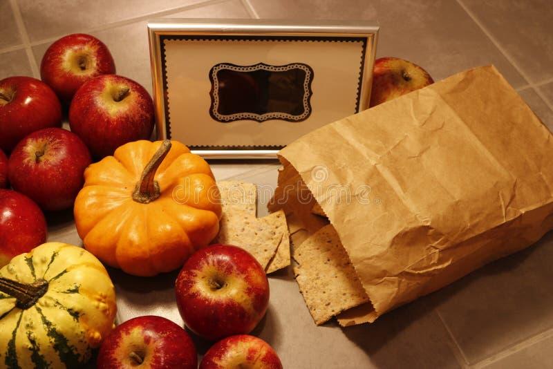 Skott för hög vinkel av en grupp av röda äpplen, miniatyrpumpor och knaprigt bröd royaltyfria foton