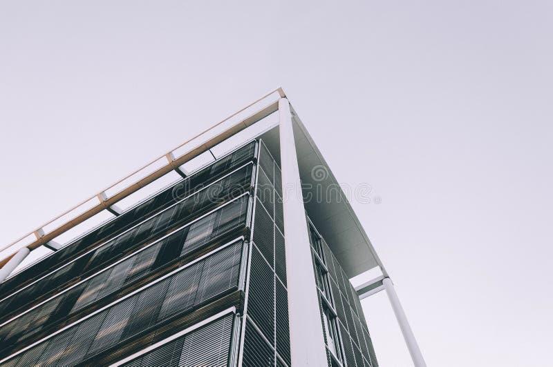 Skott för låg vinkel av hörnet av en hög affärsbyggnad arkivfoto