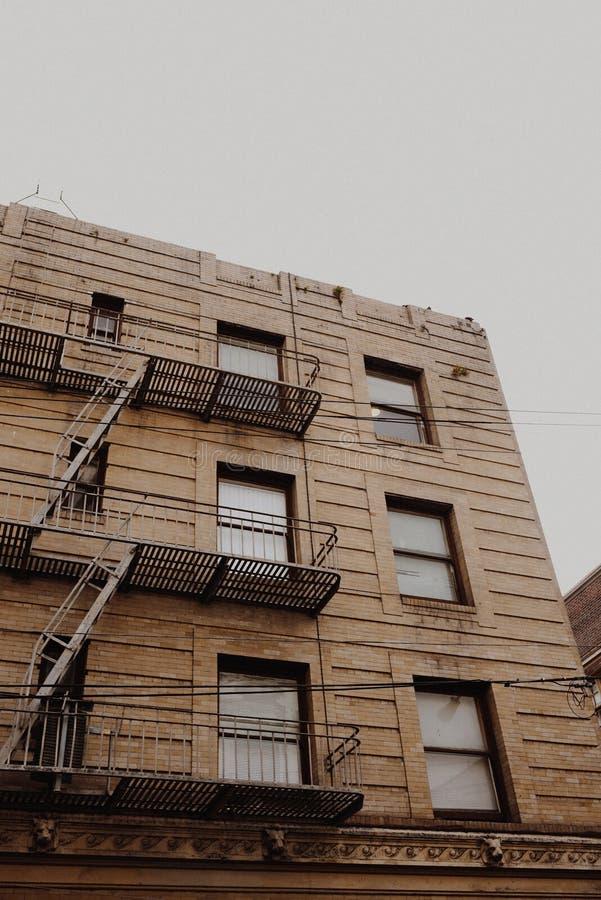 Skott för låg vinkel av hyreshusar med den nöd- trappuppgången på sidan nära fönster arkivfoto