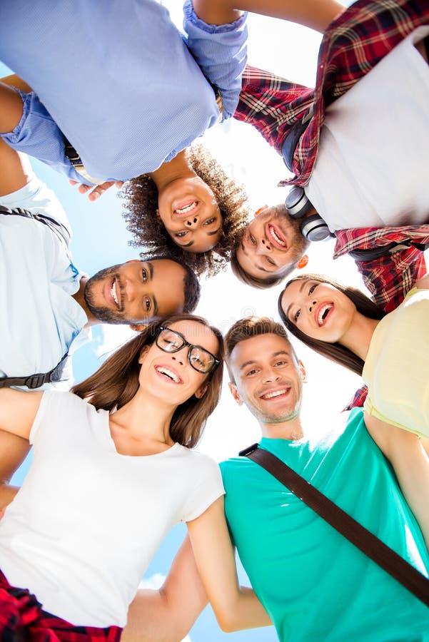 Skott för låg vinkel av sex internationella studenter med toothy leenden, royaltyfri fotografi