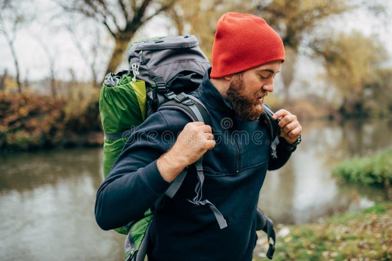 Skott för sidosikt av den unga fotvandraremannen som fotvandrar i berg med loppryggsäcken Skäggig man för handelsresande som kopp arkivfoton