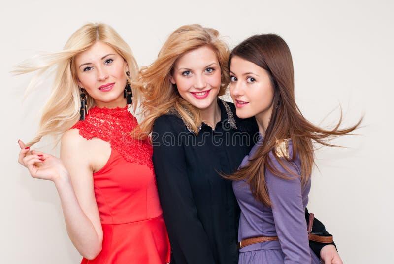 Skott för studio för tre lyckligt härligt modekvinnor royaltyfri foto