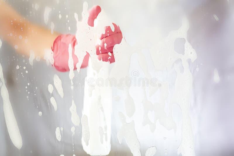 Skott till och med exponeringsglashänder med begrepp f för hushållning för trasa- och sprejflaska rengörande glass royaltyfri bild