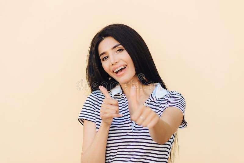 Skottet av den attraktiva europeiska kvinnlign ger upp den dubbla tummen, har positivt uttryck, har vita tänder med konsoler som  arkivbild