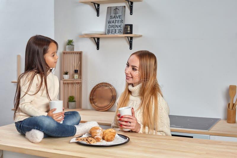 Skottet av den gladlynta modern och dottern sitter tillsammans på köksbordet, dricker varmt te i morgon, har angenäm vänskapsmatc royaltyfri bild