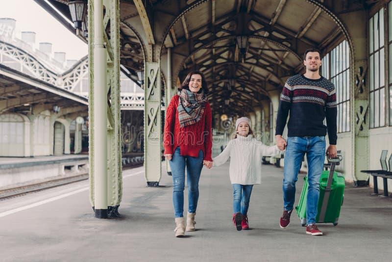 Skottet av den lyckliga familjen som går att ha trevlig tur under ferier, bär påsen, går på plattformen för järnvägstationen och  arkivbild