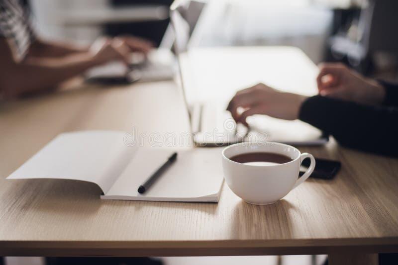 Skottet av en kvinna` s räcker maskinskrivning på ett bärbar datortangentbord, med en kopp av varmt kaffe nära arkivfoto