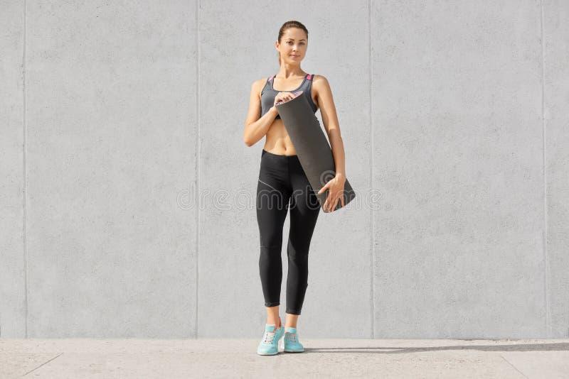 Skottet av godan som ser iklädda sportsclothes för den sportiga slanka kvinnan, håll som är matta för att ha konditionutbildning, royaltyfri bild