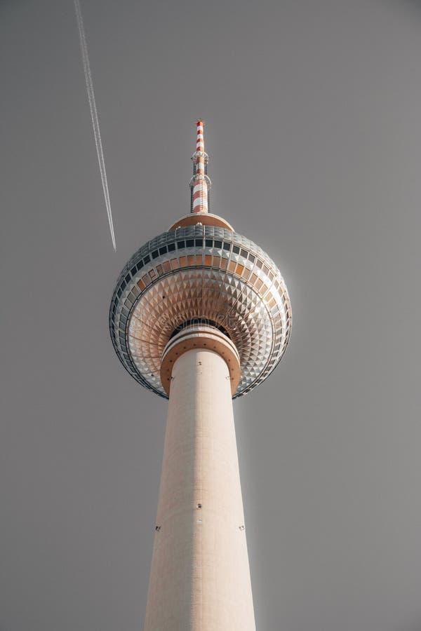 Skottet för den låga vinkeln av ett härligt högväxt vitt torn i Berlin kallade Alexanderplatz med en grå himmel royaltyfria bilder