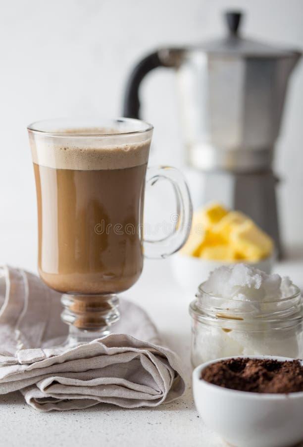 Skottsäkert kaffe Ketogenic keto bantar coffe som blandas med kokosnötolja och smör Kopp av skottsäkert kaffe och royaltyfria bilder