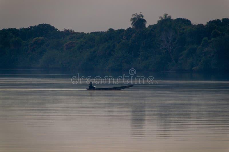 Skovel i roddbåt på den Gambia floden arkivbild