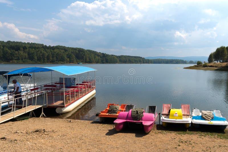 Skovel och turist- fartyg på sjön Vlasina, Serbien arkivbild