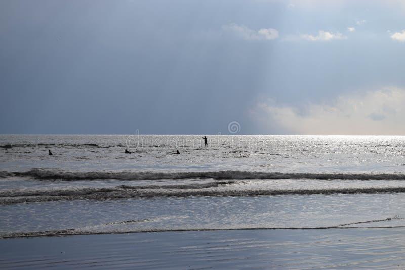 skovelbräde och surfare på det fridsamma havet arkivfoto