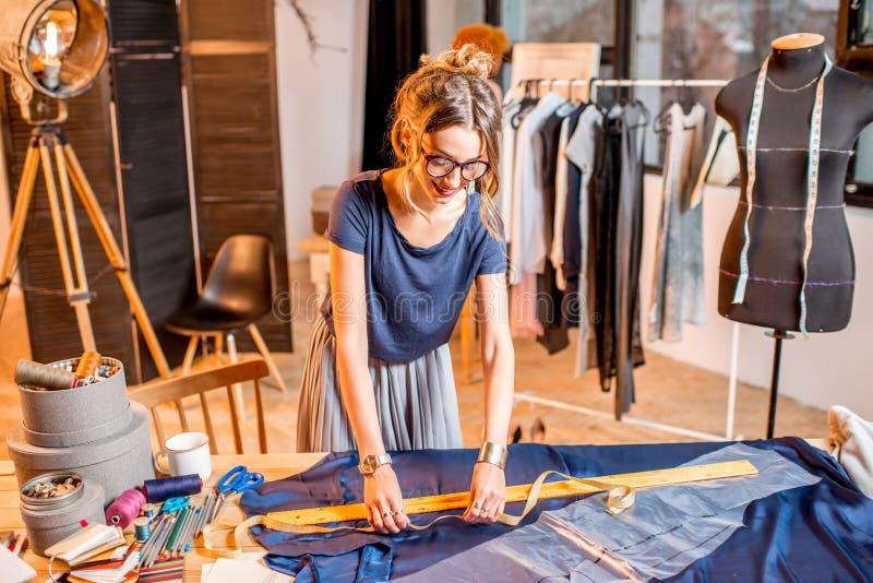 Skräddare för ung kvinna som arbetar med kläder royaltyfria bilder