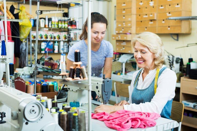 Skräddare som arbetar på symaskinen arkivbild