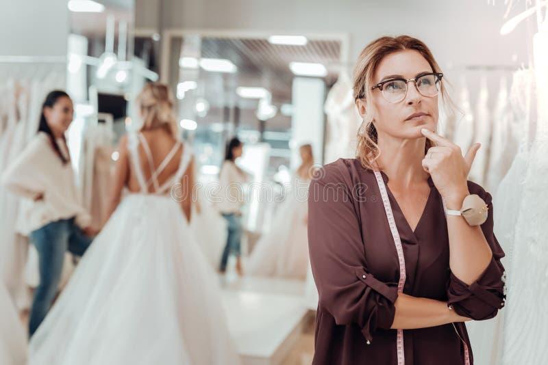 Skräddare som tänker om designen för hennes nya klänning royaltyfri fotografi