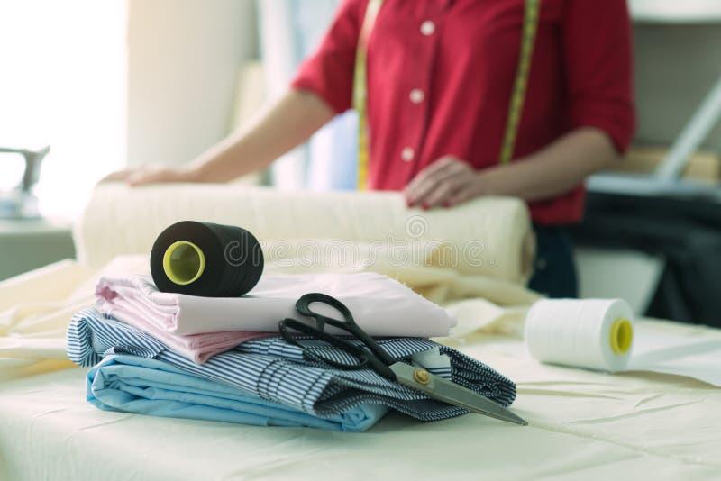 Skräddarekvinna i atelierdesignen som arbetar med sömnadhjälpmedel och textiltorkduken royaltyfri foto