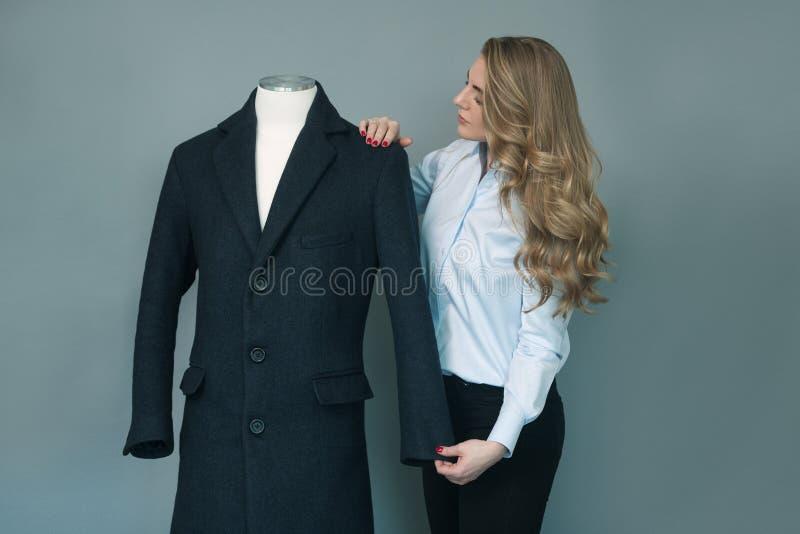 Skräddarekvinna som kontrollerar det nya sydde vinteromslaget på skyltdocka royaltyfri bild