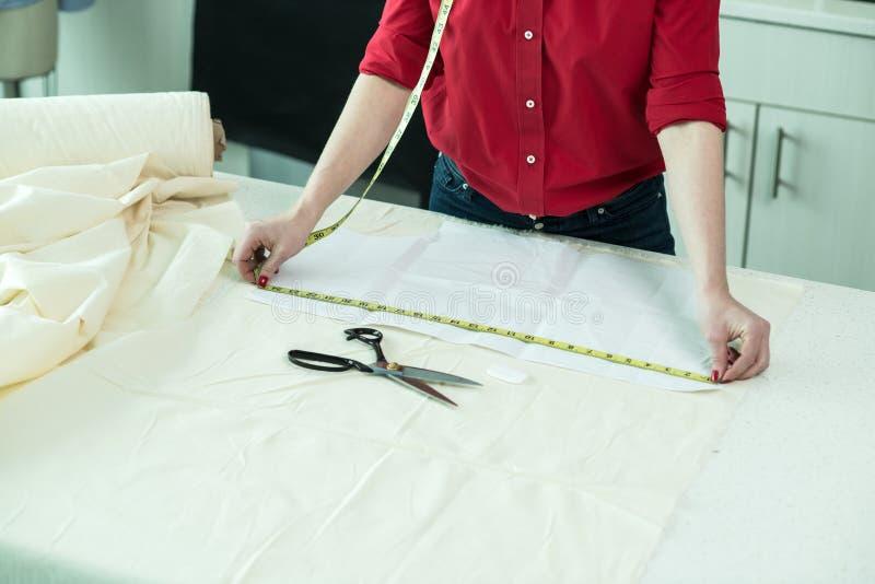 Skräddarekvinna som mäter ett stycke av textiltorkduken i atelieren arkivfoton