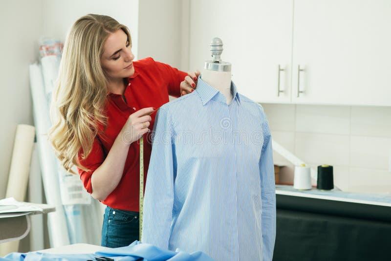 Skräddarekvinna som mäter skjortan på en skyltdocka med att mäta linjen i atelieren royaltyfri bild