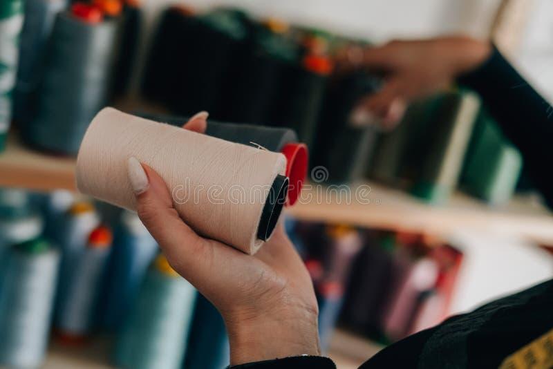 Skräddarekvinna som väljer den färgrika tråden royaltyfri bild