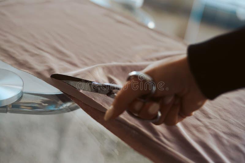Skräddarekvinnahänder som arbetar på tyg arkivbilder