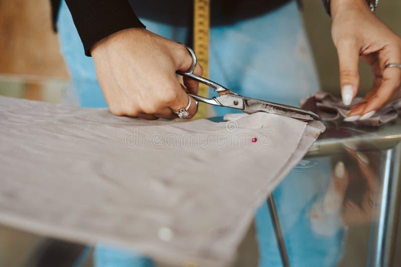 Skräddarekvinnahänder som arbetar på tyg royaltyfria foton