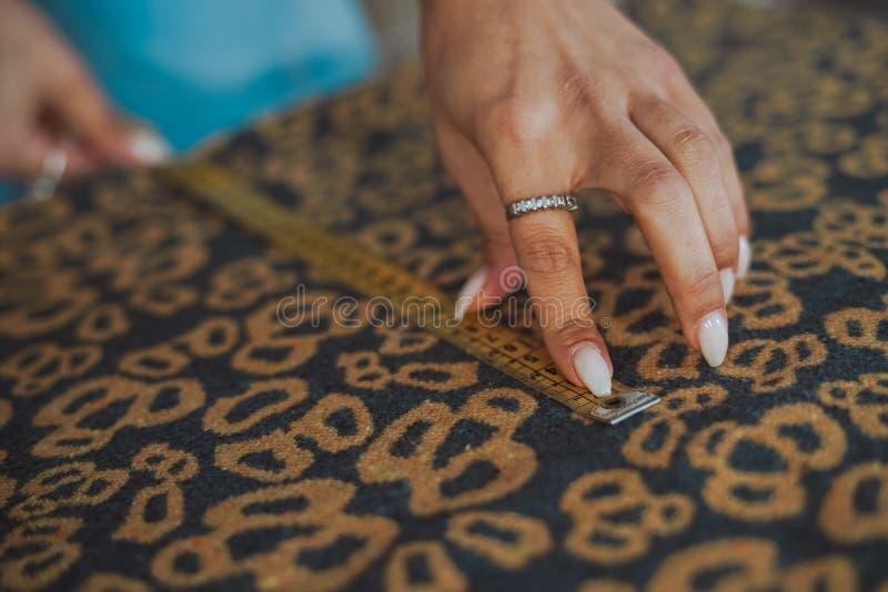 Skräddarekvinnahänder som arbetar på tyg royaltyfri fotografi