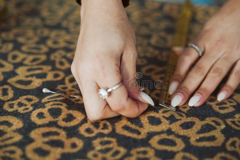 Skräddarekvinnahänder som arbetar på tyg royaltyfri foto
