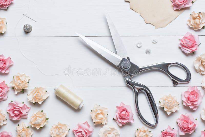 Skräddaren scissors med sömnadhjälpmedel på den vita trätabellen med ros arkivfoton