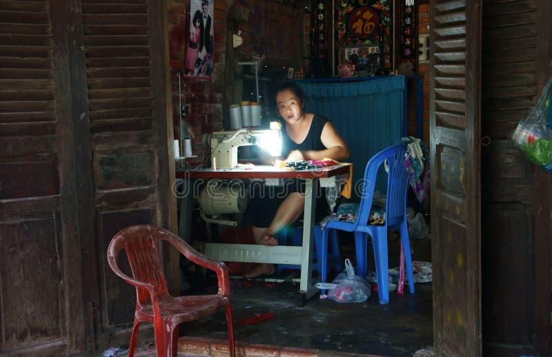 Skräddaresömnad som hemma beklär vid symaskinen royaltyfria bilder