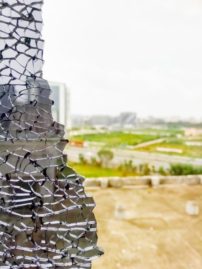 Skrälld fram stadssikt från brutet svart fönsterexponeringsglas Hål i fönster vid kulan under kamp Knarrande spridning i brutet f royaltyfri fotografi