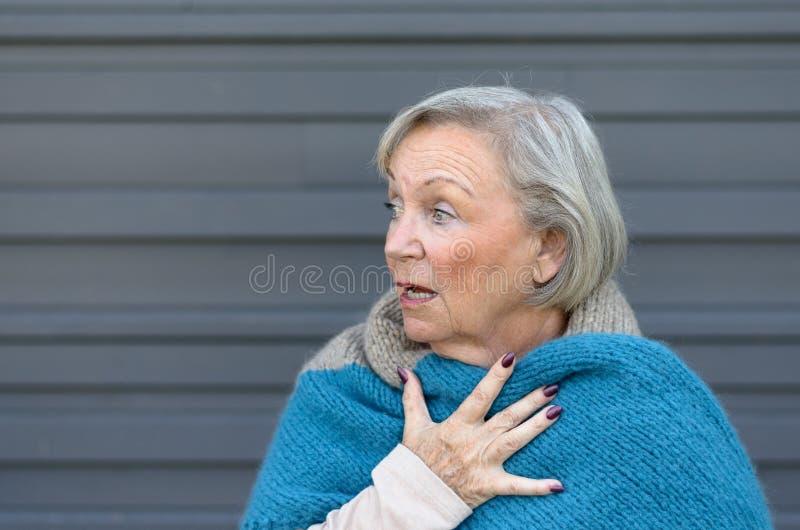 Skrämd äldre kvinna som knäpper fast hennes bröstkorg royaltyfria foton