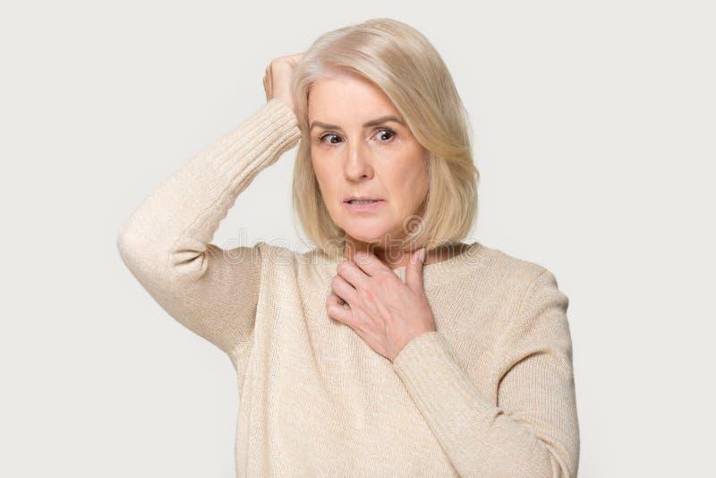 Skrämd gammal kvinna för framsidauttryck som isoleras på grå studiobakgrund arkivfoto