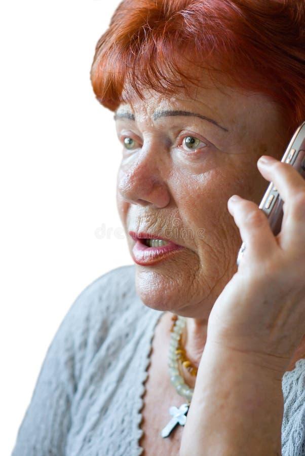 Skrämd hög kvinna med mobiltelefon royaltyfri bild
